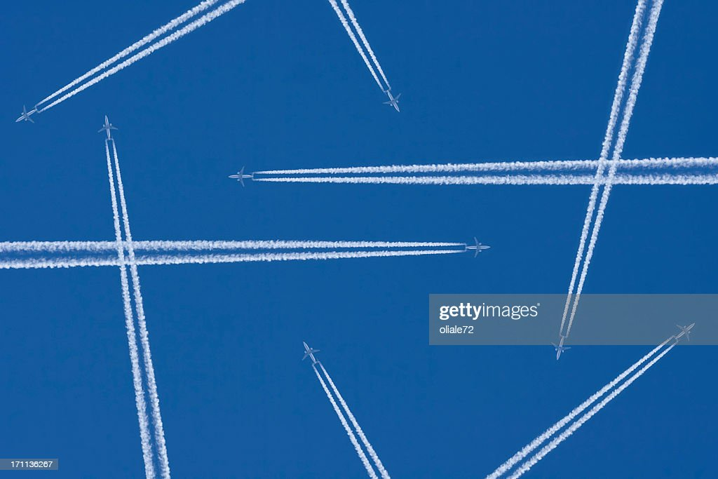 vapor trails from airplanes in mid air against a blue sky stock photo