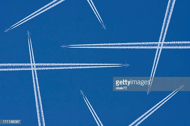 Vapor trails from airplanes in mid-air against a blue sky