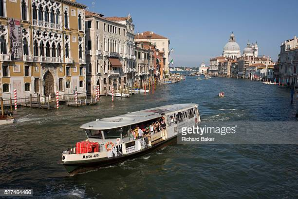 Vaporetto boat on Venice's Grand Canal seen from Ponte Accademia. At dawn the waterways are used heavily for deliveries of supplies but in the...