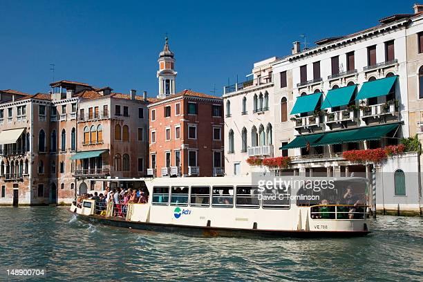 vaporetto on grand canal in cannaregio district, with chiesa dei santi apostoli bell-tower visible in background. - vaporetto stock-fotos und bilder