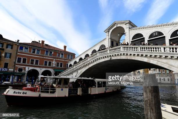 A Vaporetto or busboat passes under the Rialto bridge at the Canal Grande in Venice on April 7 2017 / AFP PHOTO / MIGUEL MEDINA