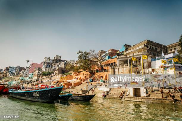Varanasi bathers in the Ganges with buildings in the background.