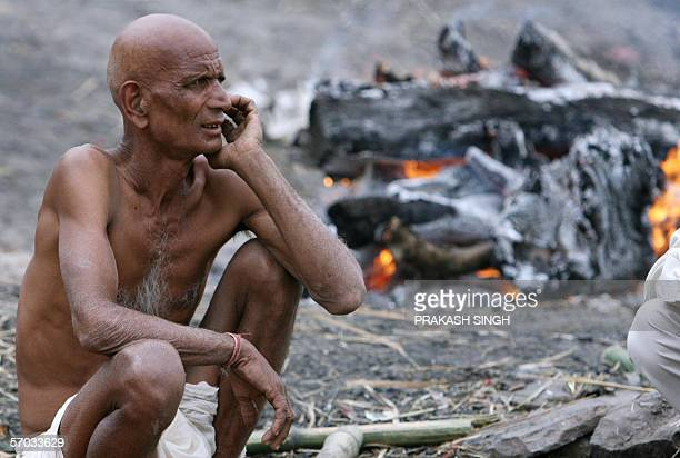 An Indian Hindu man waits for the finish of a funeral pyre of his relative at Manikarnika ghat on the banks of River Ganga, in the holy city of...