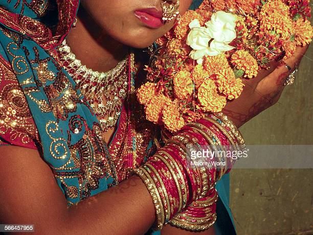 Varanasi India Detail of Indian woman wearing jewelry and traditional sari and holding flowers during hindu weading ceremony