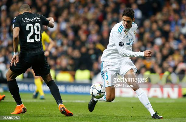 Varane and Kylian Mbappe competes for the ball with of during the UEFA Champions league round of 16 match first leg football match between Real...