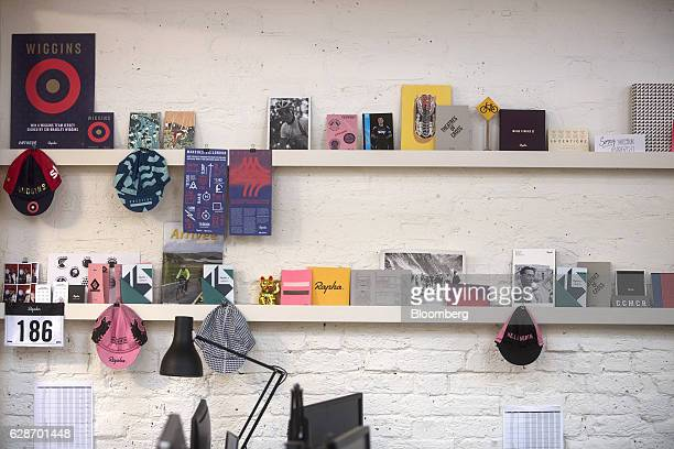 A vareity of Rapha cycling publications postcards and caps sit on display on a shelf at the Rapha Racing Ltd headquarters office in London UK on...