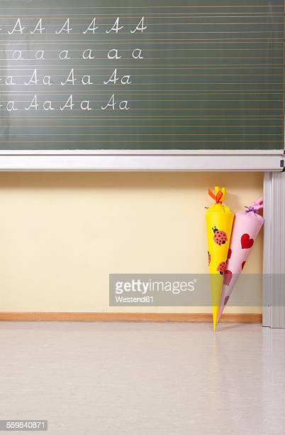 Variations of letter A at blackboard and sugar cones in classroom