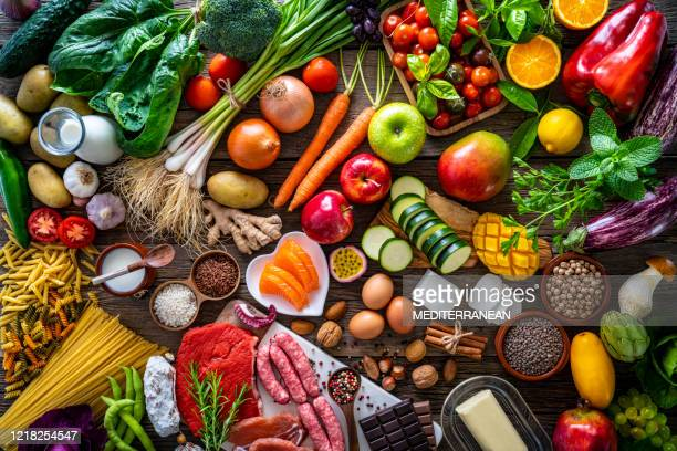 varied food carbohydrates protein vegetables fruits dairy legumes on wood - meat stock pictures, royalty-free photos & images