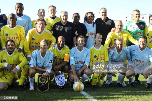 Varietes club de France's players and AS Poissy's players pose with French president Emmanuel Macron prior to a football match as part of the...