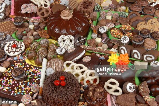 Variety / collage of Chocolate cakes, candy, pretzels, strawberries, cupcakes, cookies, icing, sprinkles, cherries, white chocolate, peanut butter cups,
