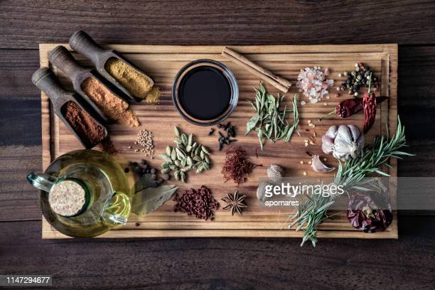variety of allspice ingredients and condiments for food seasoning on cutting board in old fashioned kitchen - spice stock pictures, royalty-free photos & images