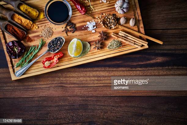 variety of allspice ingredients and condiments for food seasoning on cutting board in old fashioned kitchen - seasoning stock pictures, royalty-free photos & images