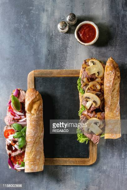 Variety of Beef baguette sandwiches with champignon mushrooms green salad onion tomatoes served on empty black chalkboard with knife salt and sauce...