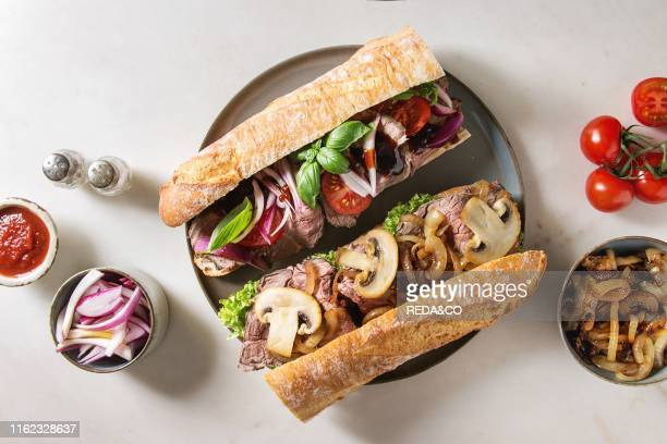 Variety of beef baguette sandwiches with champignon mushrooms green salad fried onion tomatoes served on ceramic plate with ingredients above over...