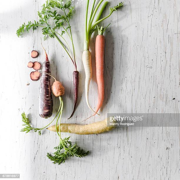 Variety of carrots on white wooden table