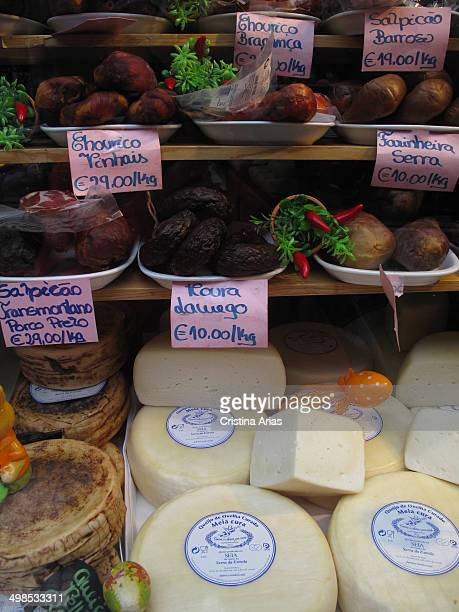Variety of cheeses and artisan sausages in the window of a store in Oporto Portugal April 2014