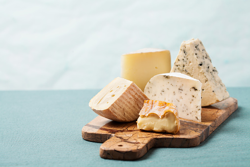 Variety of cheeses on serving board 987784172