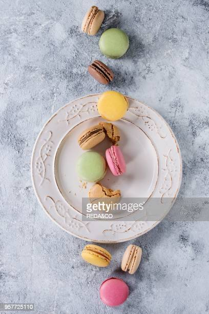 Variety of colorful french sweet dessert macaron macaroons with different fillings served on white vintage plate over gray texture background Top...