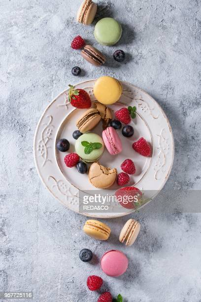 Variety of colorful french sweet dessert macaron macaroons with different fillings served on white vintage plate with spring flowers and berries over...
