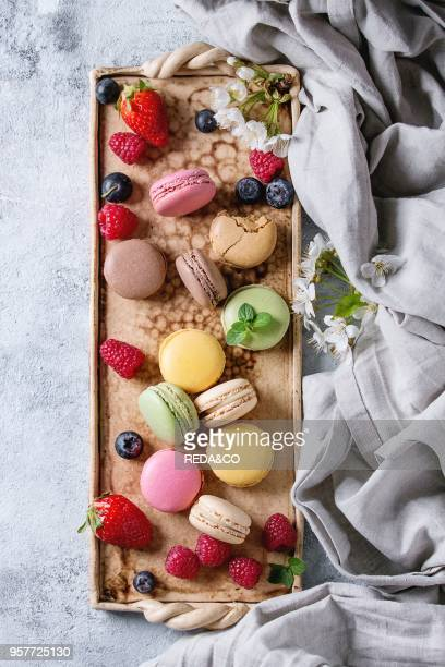 Variety of colorful french sweet dessert macaron macaroons with different fillings served on terracotta tray with spring flowers berries textile over...