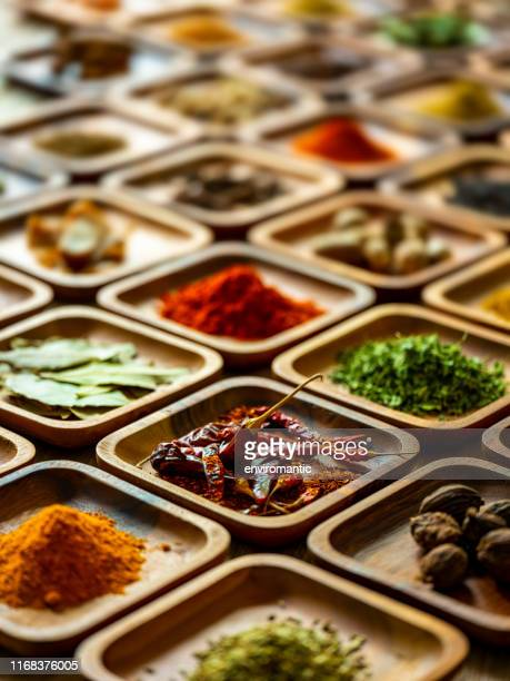 variety of colorful, organic, dried, vibrant indian food spices in wooden trays on an old wood background. - season stock pictures, royalty-free photos & images