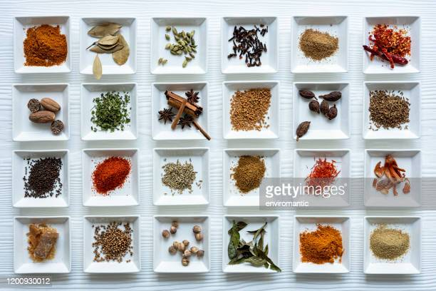 variety of colorful, organic, dried, vibrant indian food spices in white ceramic dishes on a white wood grain style table background. - spice stock pictures, royalty-free photos & images