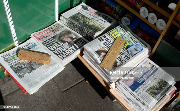 A variety of daily newspapers including The Sun for sale at a newstand in London England The Sun's headline refers to Prince Harry and his girlfriend...