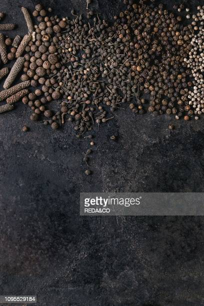 Variety of different black peppers allspice pimento long pepper monks pepper peppercorns over old black iron texture surface Food background Top view...