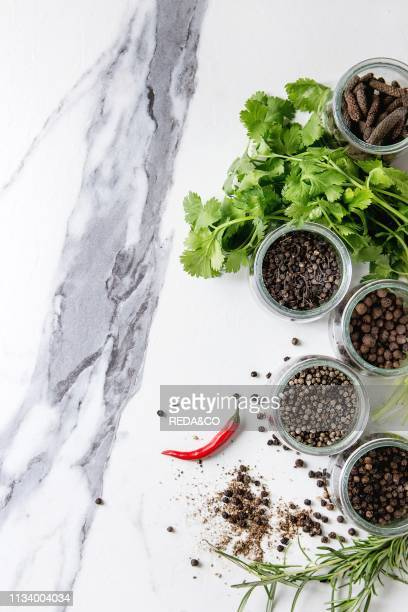 Variety of different black peppers allspice pimento long pepper monks pepper peppercorns in glass jars chili pepper and fresh herbs in plate over...