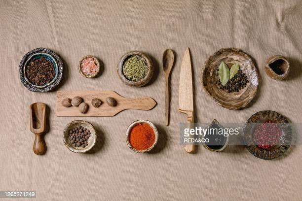 Variety of different handmade wooden and ceramic dishes bowls and cutlery with seasonings and spices over grey linen cloth as background Flat lay...