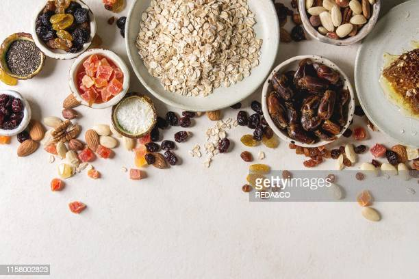 Variety of dried fruits nuts honey and oat flakes in ceramic bowls for cooking homemade healthy breakfast muesli or granola energy bars over white...