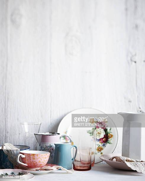 variety of drinking glasses, plates and jugs on whitewashed table - doily ストックフォトと画像
