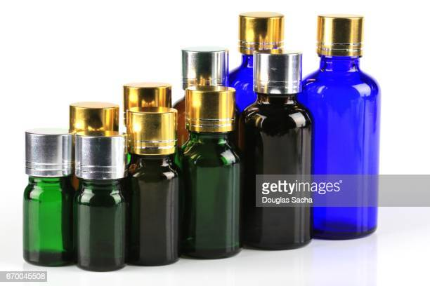 variety of essential oil bottles of different colors and sizes - tea tree oil stock photos and pictures