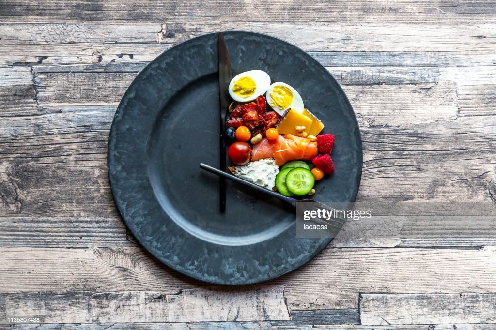 variety of food on round plate, intermittent fasting : Stock Photo