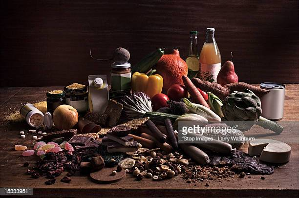a variety of fresh and processed foods in a heap on a table - nature morte photos et images de collection