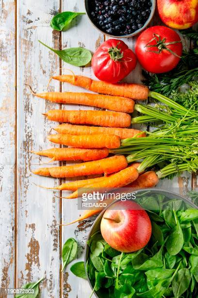 Variety of fresh fruits vegetables and berries carrot spinach tomatoes red apples blueberries over white plank wooden background Flat lay space
