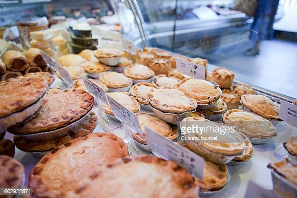 variety of fresh meat pies in refrigerator at butchers shop - savory pie stock photos and pictures