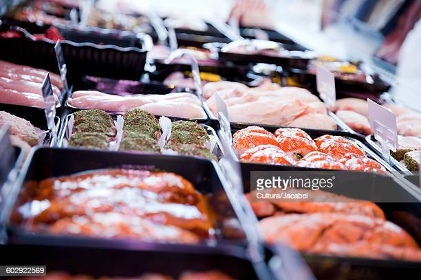 Variety of fresh meat products in refrigerator at butchers shop