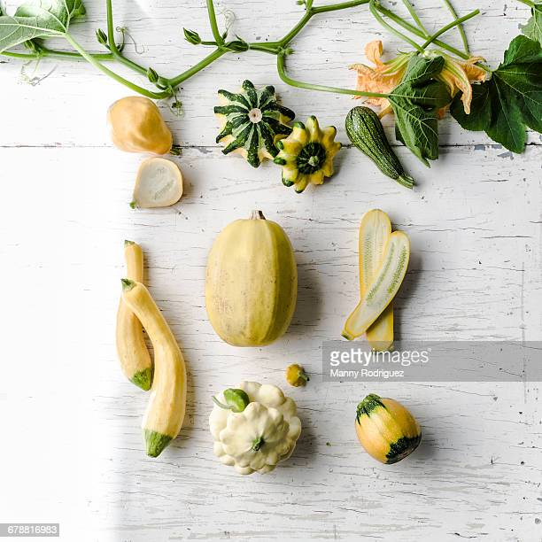 Variety of gourds on white wooden table