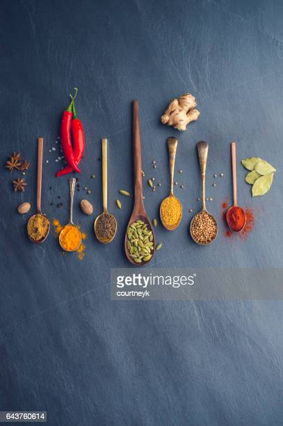 Variety of herbs and spices on slate background.
