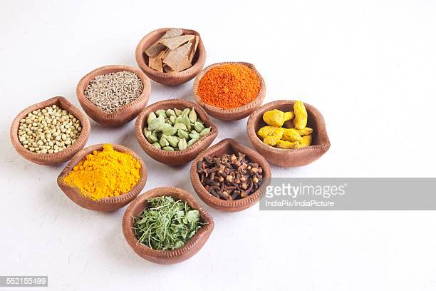 Variety of Indian spices in diyas on white background
