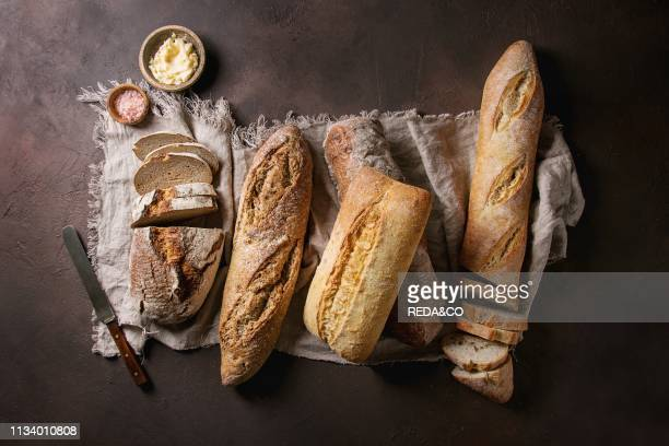 Variety of loafs fresh baked artisan rye white and whole grain bread on linen cloth with butter pink salt and vintage knife over dark brown texture...