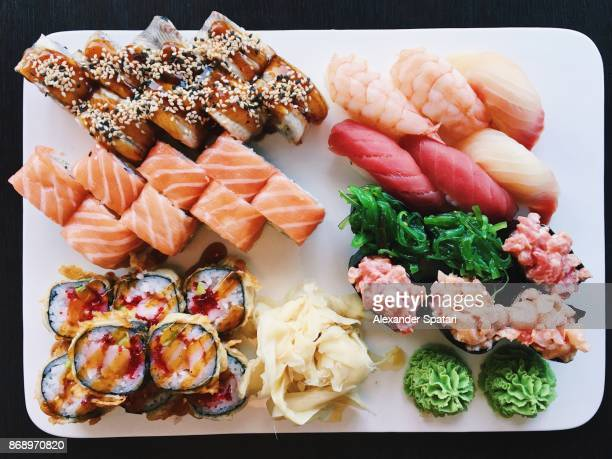 Variety of nigiri and roll sushi on a plate, view directly from above