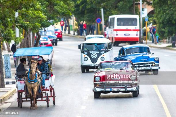 Variety of old cars and a horsedrawn carriage interacting on the First Avenue of the resort city Aerial view