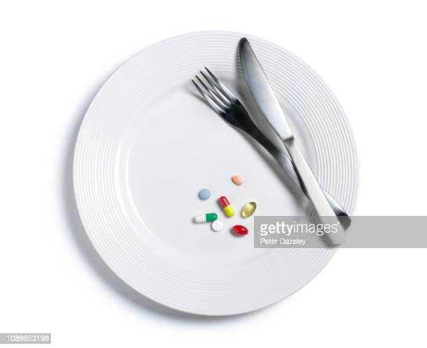 a variety of pills on a white plate - acid warning stock photos and pictures