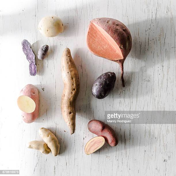 Variety of potatoes on white wooden table