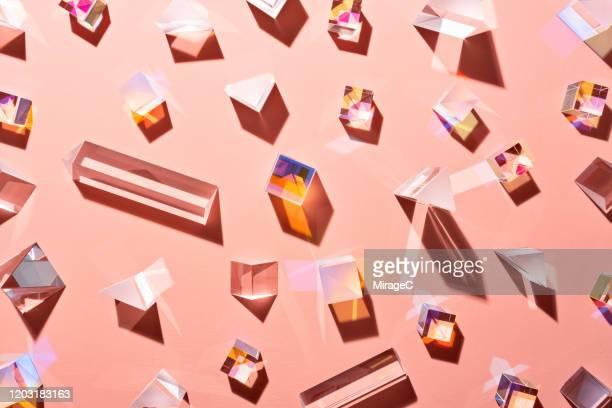 a variety of prisms on pale pink - zachtroze stockfoto's en -beelden