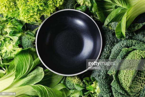 Variety of raw green vegetables salads lettuce bok choy corn broccoli savoy cabbage round empty black ceramic bowl Food background Top view space for...