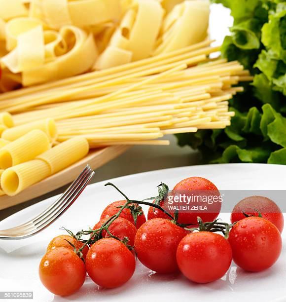 Variety of raw pasta and fresh vine tomatoes