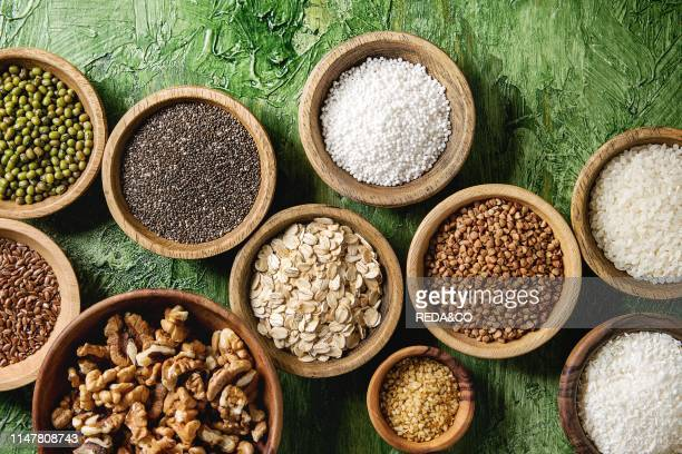 Variety of raw uncooked grains superfood cereal chia linen. Sesame. Mung bean. Walnuts. Tapioca. Wheat. Buckwheat. Oatmeal. Coconut. Rice in wooden...